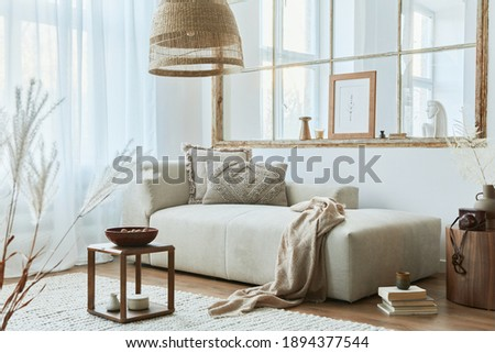 Stylish interior of living room with design modular sofa, furniture, wooden coffee table, rattan decoration, mock up picture frame, pillow, dried flowers and elegant  accessories in modern home decor.