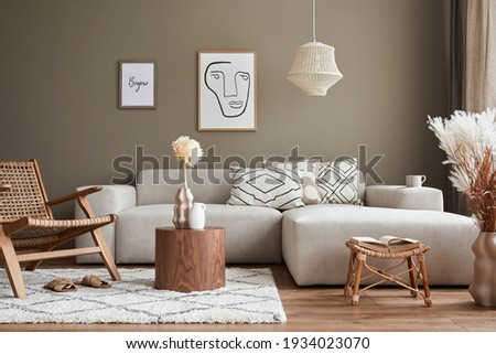 Stylish interior with design neutral modular sofa, mock up poster frames, rattan armchair, coffee tables, dried flowers in vase, decoration and elegant personal accessories in modern home decor.
