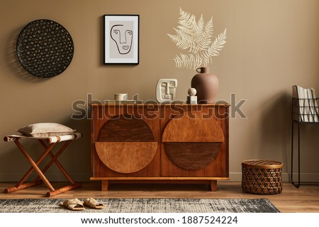 Stylish interior with design wooden commode, stool, dried flowers in vase, unique decoration, carpet, mock up poster frame and elegant personal accessories. Modern living room in classic house.