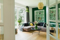 Stylish interior with sofa, colors pillows, flowers and wooden floor. Sunny and bright living room with big window and design commode..