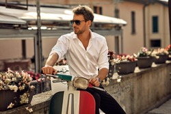 Stylish italian man wearing white shirt and sitting on classic scooter