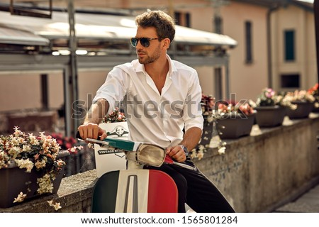 Stylish italian man wearing white shirt and sitting on classic scooter