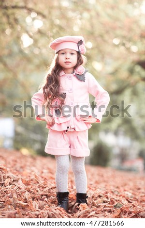 Stock Photo Stylish kid girl 5-6 year old wearing trendy winter jacket, shorts and hat standing in fallen leaves outdoors. Looking at camera. Autumn season. Posing child girl.
