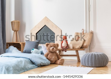 Stylish kid's bedroom in tenement house. Grey pouf on the parquet, wooden table with bags and toys, bed with blue bedding.