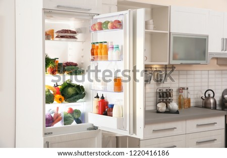 Stylish kitchen interior with refrigerator full of products