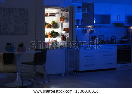 Stylish kitchen interior with refrigerator full of products at night