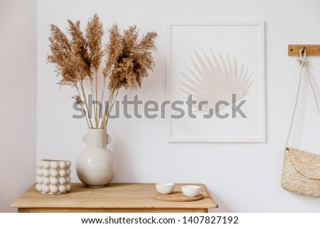 Stylish korean interior of living room with brown mock up poster frame, elegant accessories, flowers in vase, wooden shelf and hanging rattan bag. Minimalistic concept of home decor. Template. Decor. #1407827192