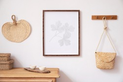 Stylish korean interior of living room with brown mock up poster frame, elegant accessories, boxes, wooden shelf and hanging rattan bag leaf. Minimalistic concept of home decor. Template. Bright room.