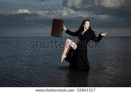 Stylish lady in the black coat with case standing in the dark water
