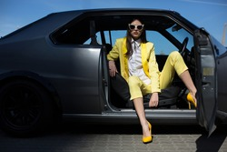 Stylish lady sitting in the car with opened door. Fashion girl driving a car in a suit. Posh girl in a sportcar.