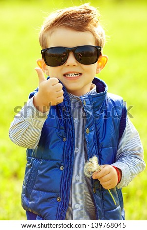 Stylish laughing baby boy with ginger (red) hair in trendy sunglasses and blue jacket standing in the park, holding dandelion and showing thumb up (ok). Hipster style. Sunny weather. Outdoor shot