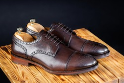 stylish leather brown shoes against a dark background. handmade shoes