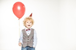 Stylish little boy in cone hat holding air balloon isolated on white
