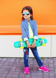 Stylish little girl child with skateboard over orange background