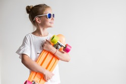 Stylish little girl child with skateboard over white background