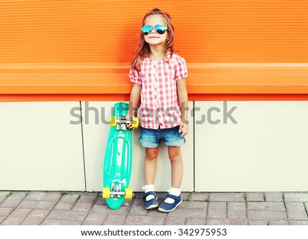 Stylish little girl child with skateboard wearing a sunglasses and checkered shirt over orange background