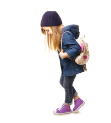 Stylish little girl in denim clothing, sneakers and backpack standing on a white background