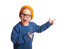 Stylish little school boy shouting. Toddler kid wearing fashion yellow hat and glasses isolated on white background. Happy smiling child with pointing fingers.