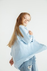Stylish little smiling girl posing in casual clothes isolated on white studio background. Caucasian blonde female model in shirt and jeanse. Human emotions, facial expression, childhood, fashion.
