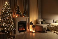 Stylish living room interior with beautiful fireplace, Christmas tree