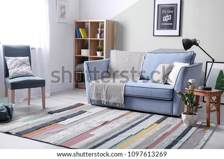 Stylish living room interior with comfortable sofa and armchair