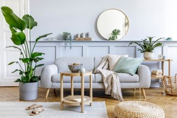 Stylish living room interior with design grey sofa, coffe table, pouf, basket, shelf, mirror, tropical plants, decoration, carpet, pillows and elegant personal accessories in modern home decor.