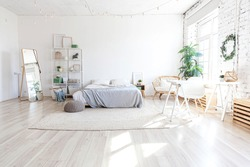 Stylish loft bedroom interior. Spacious design apartment with light walls large windows big bed. Clean modern decoration with elegant furniture in minimalist Scandinavian style
