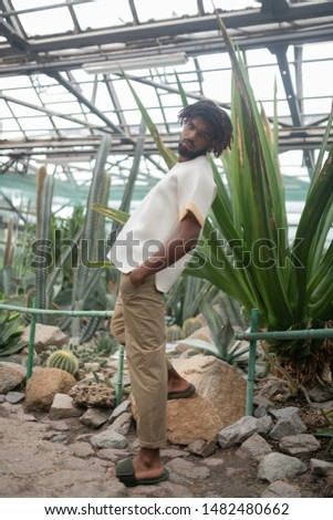 Stylish male model. Stylish male model wearing trousers and t-shirt promoting clothing while posing