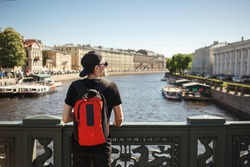 Stylish male tourist with backpack looking to cityscape on the embankment of Griboyedov canal in St. Petersburg, Russia.