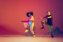 Stylish man and woman dancing hip-hop in bright clothes on green background at dance hall in neon light. Youth culture, hip-hop, movement, style and fashion, action. Fashionable portrait.