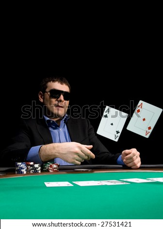 Stylish man in black suit folds two aces in casino poker at Las Vegas - stock photo