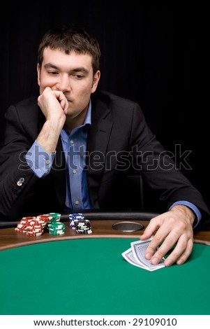 Stylish man in black suit thinking before bet in the casino