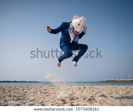 Stylish man in funny mask and suit jumps on beach. Unicorn have fun on the shore and enjoys vacation. Elegant traveler on background of sea and sky