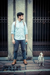 stylish man in the street with a jack russel in front of a wall