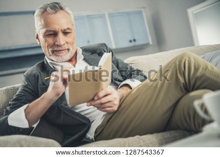 Stylish man. Stylish man wearing fashionable beige trousers and grey suit sitting on sofa looking in his notebook