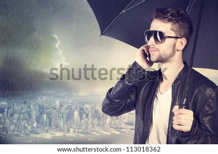 Stylish man talking on his cellphone in the rain