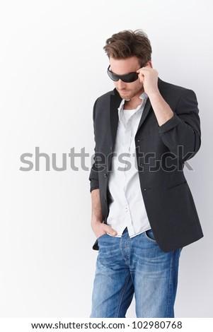 Stylish man wearing sunglasses, standing over white background.