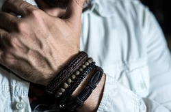 Stylish man wears wrist wooden and leather bracelets