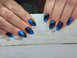 stylish manicure design in the style of minimalism, black gel polish. Blue marble pattern. Manicure trend