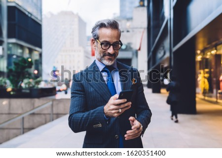 Stylish mature male in dark well-fitting business suit and glasses standing with slight smile on face in New York street and holding smartphone in hand  Stock photo ©
