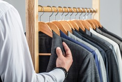 Stylish men's suit. Male suits hanging in a row. Men clothing, boutiques. Man suit, tailor in his workshop. Fashion man in classical costume suit. Tailor, tailoring.