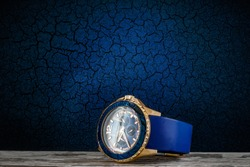 Stylish men's watch with a blue rubber strap and gold rim on a wooden surface against the background of a crackling blue wall.
