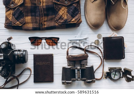 Stylish men set to travel, money, passport, airplane, hat, shoes, shirt, binoculars, sunglasses, camera, map, on vintage wooden background.