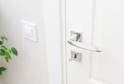Stylish metal door handle and escutcheon for lock with key. Close-up elements of the interior. White door and white wall with switch