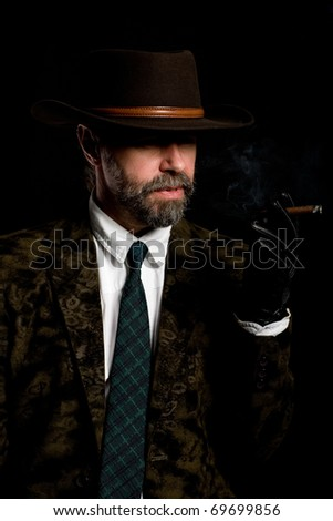 Stylish middle aged man smoking a cigar.