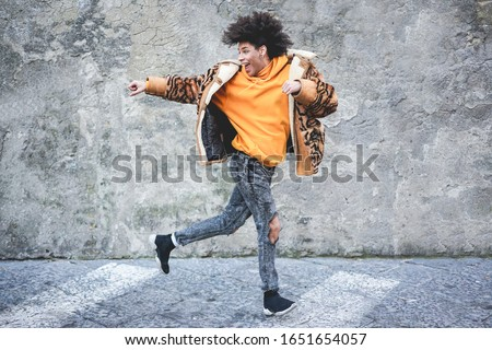 Stylish millennial guy dancing around city street outdoor - Young man having fun outside wearing trendy clothes - Z generation and fashion concept - Focus on his face Stockfoto ©