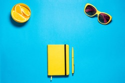 Stylish minimalistic feminine fashion workspace. Bright yellow glasses and diary with pen, pirces oranges against deep blue copy space. Top view.