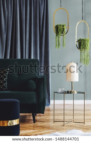 Stylish minimalistic interior of living room with design green velvet sofa, pouf, coffee table, pillow, marble table lamp, hanging gold flowerbeds and elegant accessories. Eucalyptus color. Template.