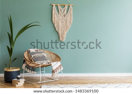 Stylish minimalistic interior of living room with design rattan armchair, tropical plant in basket, plaid, beige macrame on the wall and elegant accessories. Eucalyptus color of wall. Copy space.