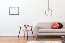 Stylish minimalistic living room with design grey sofa, geometric lamp, coffee table, pillows and elegant accessories Mock up posters frame on the white walls. Minimalistic home decor.